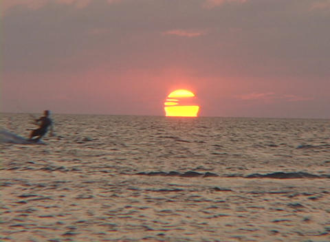 A windsurfer surfs across the water in silhouette against... Stock Video Footage