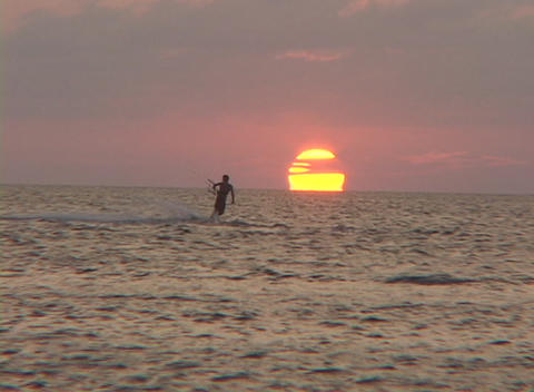 A windsurfer surfs across the water in silhouette against the sun Footage