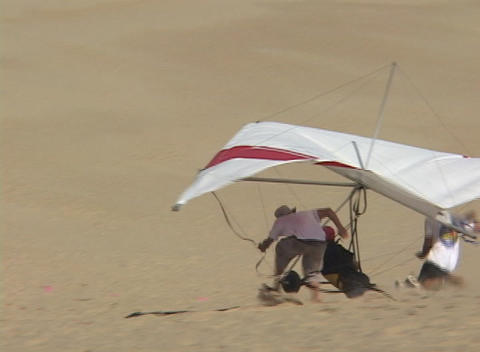 A hang-glider falls into the sand after an unsuccessful trial run Footage