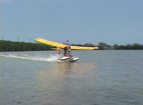 An ultralight airplane skids across the water and begins to take-off into the air Footage