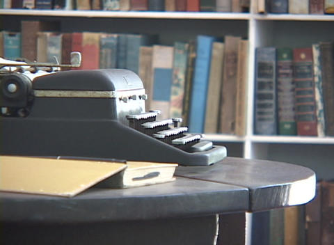 An antique typewriter sits on a table in a library Stock Video Footage