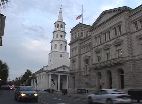 Cars drive by a white church with a tall steeple and a government building Footage