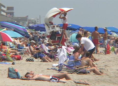 Sunbathers lounge on a crowded Florida beach Stock Video Footage