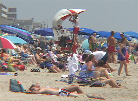Sunbathers lounge on a crowded Florida beach Footage