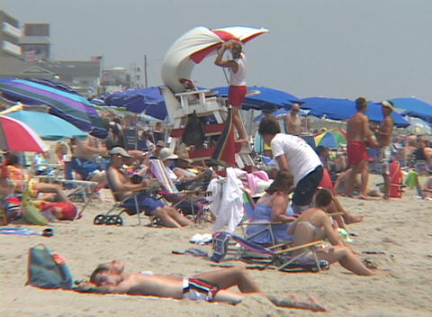 Sunbathers lounge on a crowded Florida beach Stock Video Footage