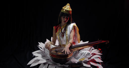 Saraswati holding pearl beads and her veena while sitting on a big flower, 4k Live Action