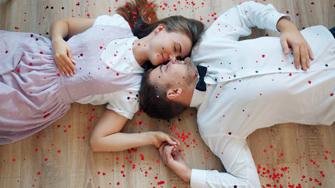 Beautiful couple lying on floor face to face while heart shape confetti falling Live Action