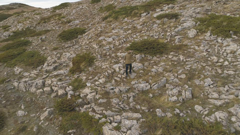 Man tourist walk on sharp rock peak. Alone hiker in green jacket enjoy view Live Action