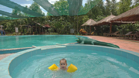 Little Girl Jumps into Small Round Swimming Pool at Hotel Footage