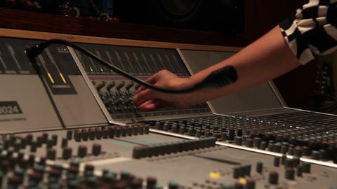 Recording studio music mixing desk console with engineer hand turning nob Bild