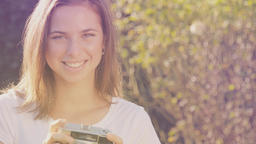 Portrait of a happy young woman with retro camera smiling and taking photos Footage