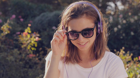 Beautiful young hipster girl with headphones and sunglasses listening to music Footage