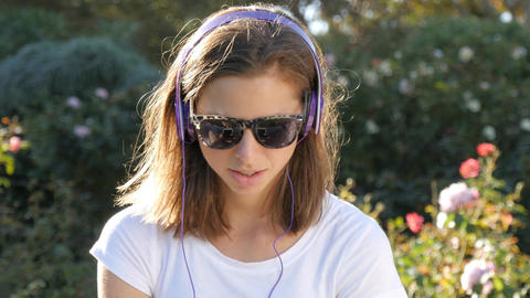 Attractive woman in 20s listening to music with headphones outdoors in park Footage