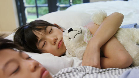 Siblings sleeping on bed in the bed room 4k Live Action