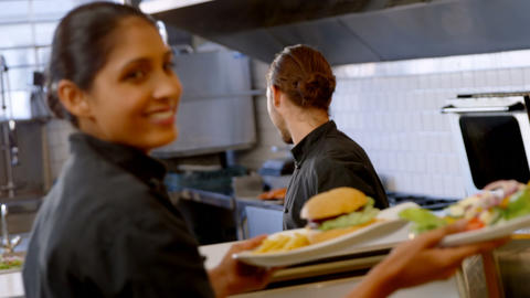 Male chef handing over meal plates to waitress 4k Live Action