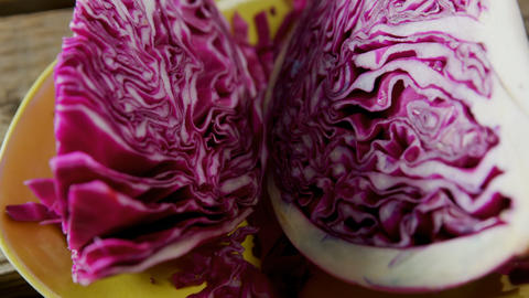 Sliced red cabbage in plate on wooden table 4k Live Action