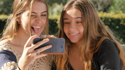 Happy teenage girls selfie shot mobile phone pulling funny faces expression Footage