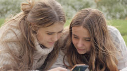 Two teenagers on phone texting and looking at social media interacting laughing Footage