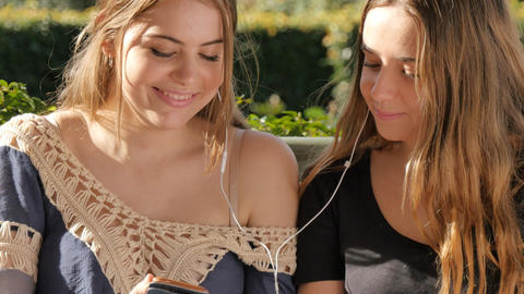 Best friends listening to music on mobile smart phone sharing headphone laughing Footage