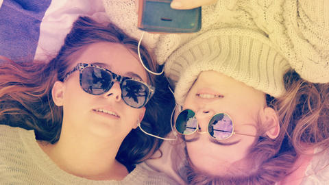 Stylish hip teenage girls with sunglasses listening to music sharing headphones Footage