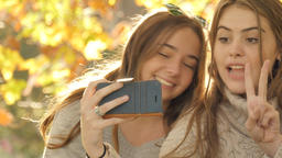 Two best friends with cell phone camera taking photos under autumn fall Footage