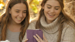Young college students girls laughing while using tablet pc autumn fall BG Footage