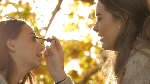 Young woman best friends applying eyeliner makeup under autumn fall tree Footage