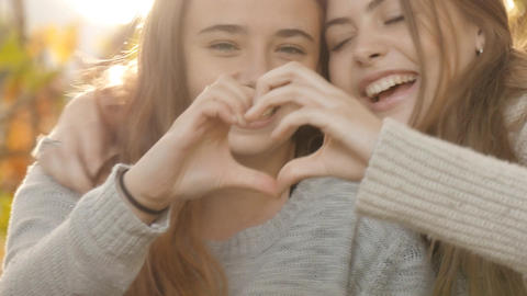 Love and affection two close young girl best friends love heart hands laughing Footage