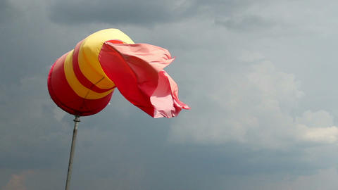 Wind sock with rainy stormy clouds background. Red and yellow Footage