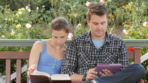 University students study on campus outdoors with book and tablet for exams Footage