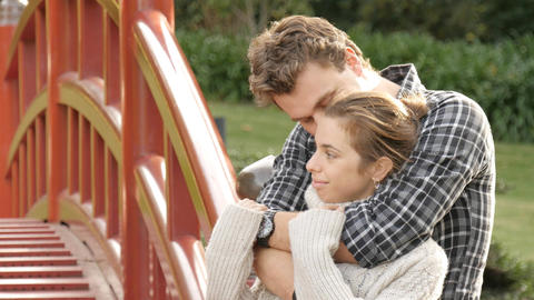 Attractive young couple in love cuddle and embrace outside in park Footage