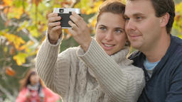 Couple using an old vintage retro style camera to take selfie autumn day Footage