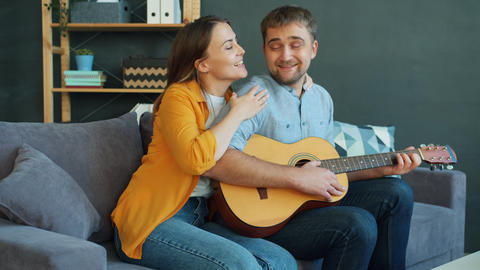 Happy couple singing playing the guitar in apartment enjoying leisure time Live Action
