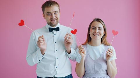 Happy youth holding hearts hiding eyes laughing enjoying romance on valentine's Live Action