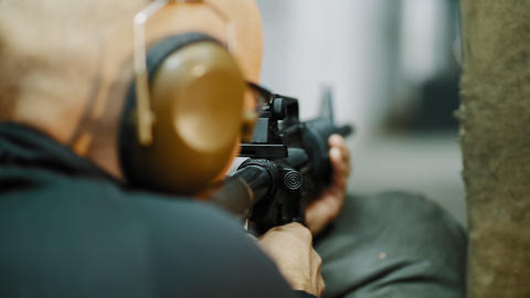 A man shoots with an automatic carbine at a shooting gallery Live Action