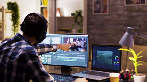Film maker pointing at the monitor in home office Live Action