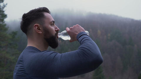 Side view of strong man with big cool beard drinking water outside against foggy Live Action