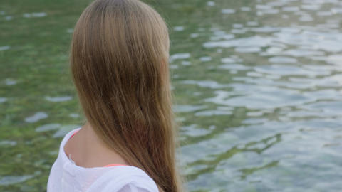 Long haired girl teenager looking sea water on summer beach. Back view teenager Live Action