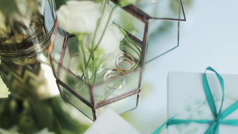 Close-up of two wedding rings on a flowers background.…, Live Action