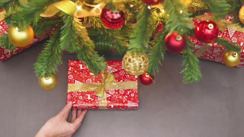 Stop motion animation of hand putting a Christmas present under the Christmas tree Animation