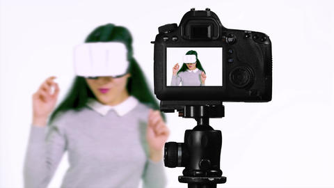 Asian teenager wearing VR goggles dances show V from behind camera vlogger concept Live Action