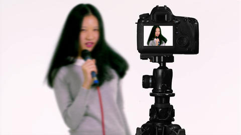 Asian teenager singing with microphone from behind camera vlogger concept Live Action