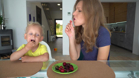 Loving son feed his mother with cherry berry. Gimbal smooth camera movement Live Action