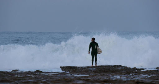 Surfer looking at ocean waves before surfing Footage