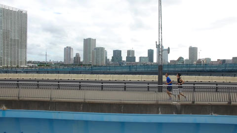 International and Japanese runner training on bridge Tokyo Drone aerial shot sid ビデオ