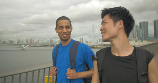 International friends walking together on Bridge with Tokyo city background Footage