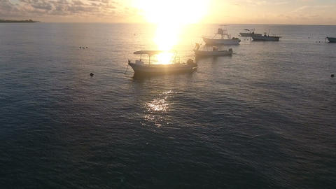 Flying drone shot of sunset over the sea passing a fisherman on his boat ビデオ
