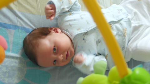 Little Cute Baby Boy Lying In Crib With Toy Footage
