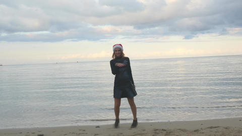 Funny woman in Santa hat funny walking by the sea Live Action