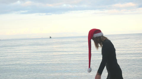 Woman in Santa hat sadly walking by the sea Live Action
